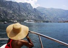 La mujer en un sombrero de paja de ala ancha se sienta en barco y mira el mar y las montañas Visión posterior Imagen de archivo
