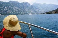 La mujer en un sombrero de paja de ala ancha se sienta en el barco y mira el mar y las montañas Visión posterior Imagenes de archivo