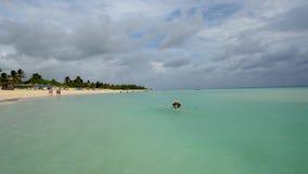 La mujer en un sombrero de paja flota en el océano cerca de la playa almacen de metraje de vídeo