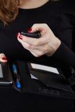 La mujer en un suéter negro sostiene el teléfono móvil Imagen de archivo
