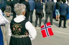 La mujer en un traje noruego tradicional sostiene una bandera noruega Imagen de archivo