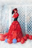 La mujer en un vestido antiguo rojo está congelando debajo de la nieve que cae Imagenes de archivo