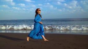 La mujer en un vestido azul corre a lo largo de una playa volcánica negra almacen de video