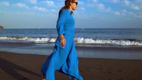 La mujer en un vestido azul corre a lo largo de una playa volcánica negra almacen de metraje de vídeo