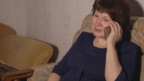 La mujer en un vestido azul se está sentando en una silla y está hablando en el teléfono imagen de archivo