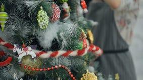 La mujer en un vestido gris es árbol de navidad artificial adornado almacen de video