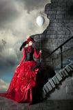 La mujer en un vestido histórico rojo está sosteniendo una bola blanca del aire Imagenes de archivo