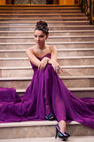 La mujer en un vestido largo se está sentando en las escaleras Foto de archivo