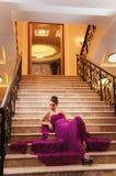 La mujer en un vestido largo se está sentando en las escaleras Imagen de archivo libre de regalías