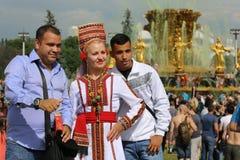 La mujer en un vestido nacional y dos hombres de una diversa nacionalidad Foto de archivo libre de regalías