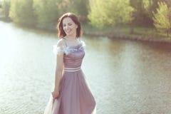 La mujer en un vestido púrpura está sonriendo fotografía de archivo libre de regalías