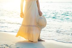 La mujer en un vestido poner crema está caminando, disfrutando de la puesta del sol hermosa Fotos de archivo