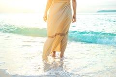 La mujer en un vestido poner crema está caminando, disfrutando de la puesta del sol hermosa Imagenes de archivo