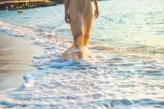 La mujer en un vestido poner crema está caminando, disfrutando de la puesta del sol hermosa Fotos de archivo libres de regalías