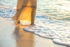 La mujer en un vestido poner crema está caminando, disfrutando de la puesta del sol hermosa Foto de archivo libre de regalías