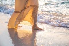 La mujer en un vestido poner crema está caminando, disfrutando de la puesta del sol hermosa Fotografía de archivo