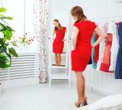 La mujer en un vestido rojo mira en el espejo y elige la ropa imagen de archivo