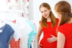 La mujer en un vestido rojo mira en el espejo y elige la ropa imagenes de archivo