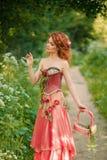 La mujer en un vestido rojo recoge las flores blancas Fotografía de archivo