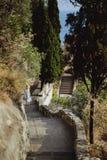 La mujer en un vestido y un sombrero hermosos del verano va abajo de las escaleras a la plataforma de observación en la colina o  fotografía de archivo