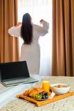 La mujer en una albornoz estira por la mañana Fotos de archivo