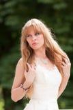 La mujer en una alineada blanca plancha el pelo Foto de archivo libre de regalías