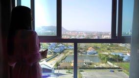 La mujer en una bata transparente rosada se destaca y mira en la ventana y el café panorámicos de las bebidas 4k Hua Hin imágenes de archivo libres de regalías
