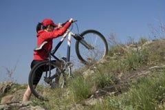 La mujer en una bicicleta de la montaña Foto de archivo libre de regalías