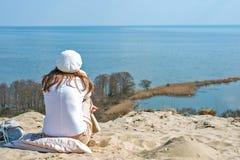 La mujer en una boina se sienta en una montaña y la mirada del mar Fotos de archivo