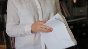 La mujer en una camisa blanca está sosteniendo un diario almacen de metraje de vídeo