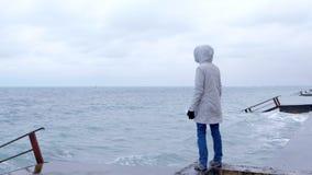 La mujer en una chaqueta blanca se coloca en la costa en las miradas de la playa en las ondas de la tormenta Visión posterior almacen de video