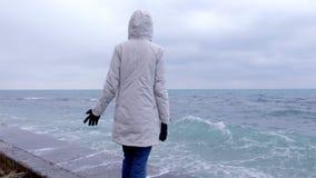 La mujer en una chaqueta blanca se coloca en la costa en las miradas de la playa en las ondas de la tormenta Vista lateral almacen de video
