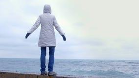 La mujer en una chaqueta blanca se coloca en la costa en los brazos de la playa extendidos y mira ondas de la tormenta Visión pos almacen de video