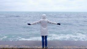 La mujer en una chaqueta blanca se coloca en la costa en los brazos de la playa extendidos y mira ondas de la tormenta Visión pos metrajes