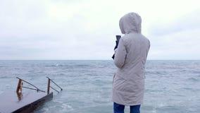 La mujer en una chaqueta blanca toma las ondas de una tormenta del teléfono móvil que se colocan en el terraplén Visión posterior metrajes