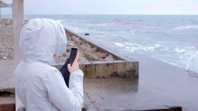 La mujer en una chaqueta blanca toma a teléfono móvil las ondas grandes de la tormenta que se colocan en el terraplén Visión post metrajes