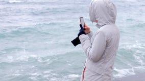 La mujer en una chaqueta blanca toma a teléfono móvil ondas grandes de la tormenta Visión posterior almacen de video