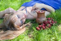 La mujer en una hierba es una fresa Fotos de archivo