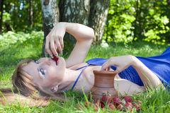 La mujer en una hierba es una fresa Foto de archivo