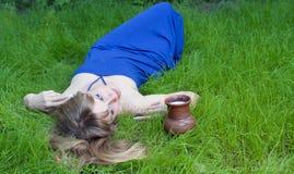 La mujer en una hierba y un jarro de leche Fotografía de archivo libre de regalías