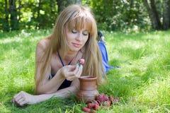 La mujer en una hierba y una fresa con leche Fotografía de archivo