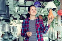 La mujer en una tienda más ligera está eligiendo la lámpara elegante y moderna Foto de archivo