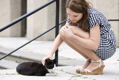 La mujer en vestido a cuadros mima el gato de la calle Imagenes de archivo