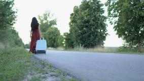 La mujer en vestido largo camina con la maleta en el camino almacen de video