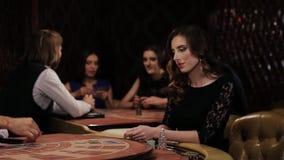La mujer en vestido negro toma la tarjeta y hace una apuesta en un casino, Blakjack metrajes