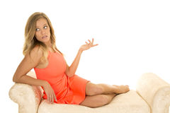 La mujer en vestido rojo se sienta cómodamente en la mirada blanca del sofá Foto de archivo libre de regalías