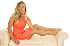 La mujer en vestido rojo se sienta en el sofá blanco subrayado Fotografía de archivo