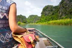 La mujer en vestido viaja en el río un fondo de montañas rocosas Imagen de archivo