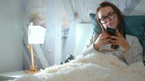 La mujer en vidrios miente en una cama y utiliza un smartphone antes de hora de acostarse