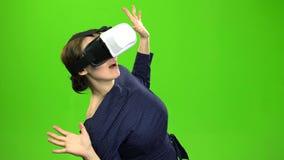 La mujer en vidrios virtuales está mirando una película interesante Pantalla verde metrajes